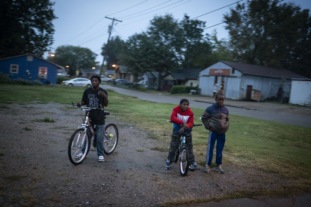 People wait to cross a street in Cleveland, Miss., Friday, Oct. 9, 2020. Distrust of the government runs deep in the Black community in Mississippi, w...