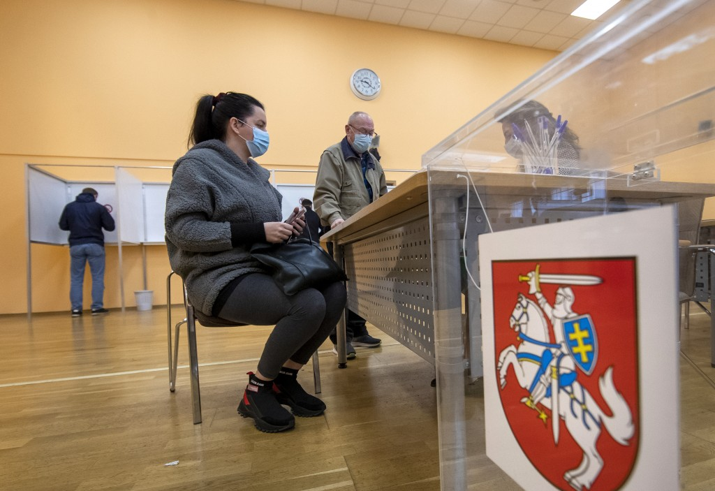 Lithuanian's, wearing face masks to protect against coronavirus, wait for ballots at a polling station during early voting in the second round of a pa...