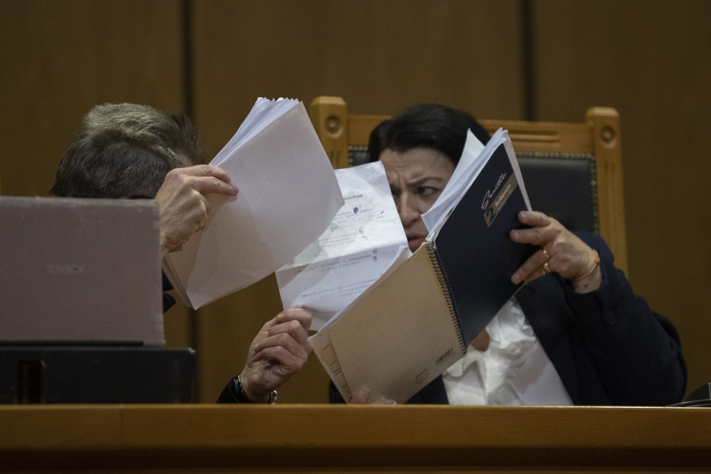 Presiding judge Maria Lepenioti consults a fellow judge as she reads the sentences during the Golden Dawn trial, in Athens, Thursday, Oct. 22, 2020. T...