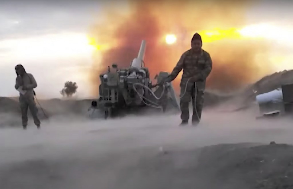 In this image taken from video released by Azerbaijan's Defense Ministry on Wednesday, Oct. 21, 2020, Azerbaijan army soldiers fire an artillery piece...