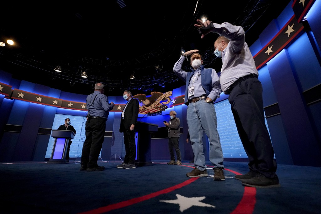 Production crew member stand on stage ahead of the final presidential debate between Republican candidate President Donald Trump and Democratic candid...
