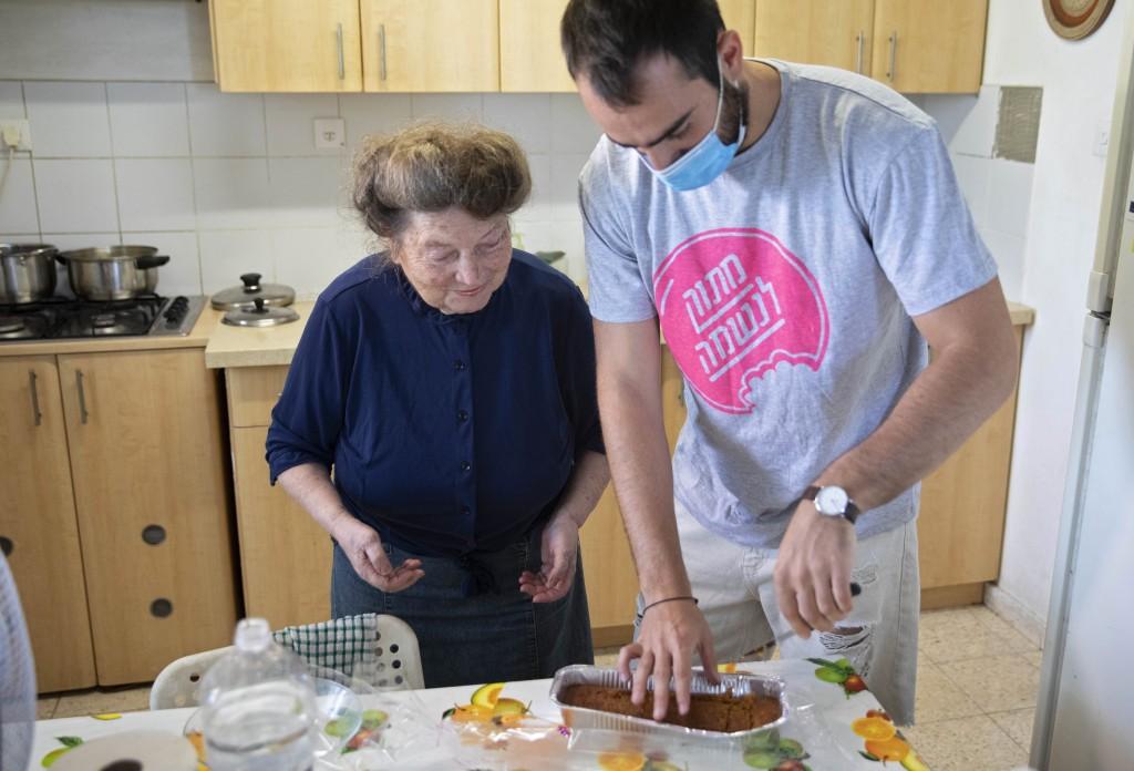 Sonia Rozenblatt, 85, tastes a cake made for her by Israeli volunteer Din Belz in the central Israeli city of Ra'anana, Thursday, Oct. 8, 2020. For th...