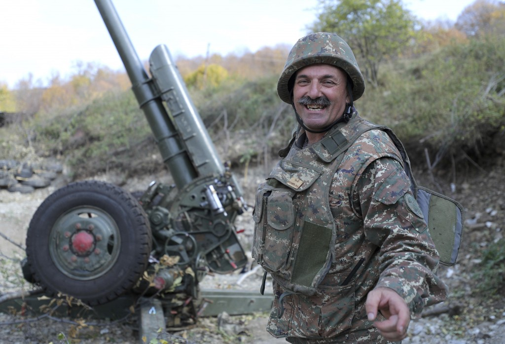 An ethnic Armenian soldier smiles as he speaks to journalists at a fighting position on the front line, during a military conflict against Azerbaijan'...