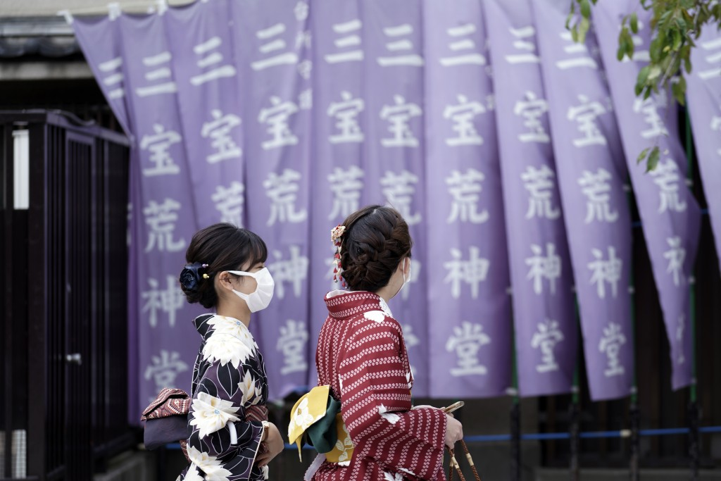 Kimono-clad visitors wearing protective masks to help curb the spread of the coronavirus walk at a shopping arcade at Asakusa district Thursday, Oct. ...