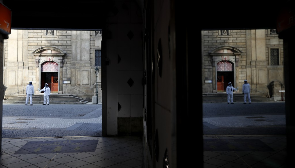 Tour guides wearing face masks are reflected in a window downtown Prague, Czech Republic, Wednesday, Oct. 21, 2020. In another desperate attempt to sl...