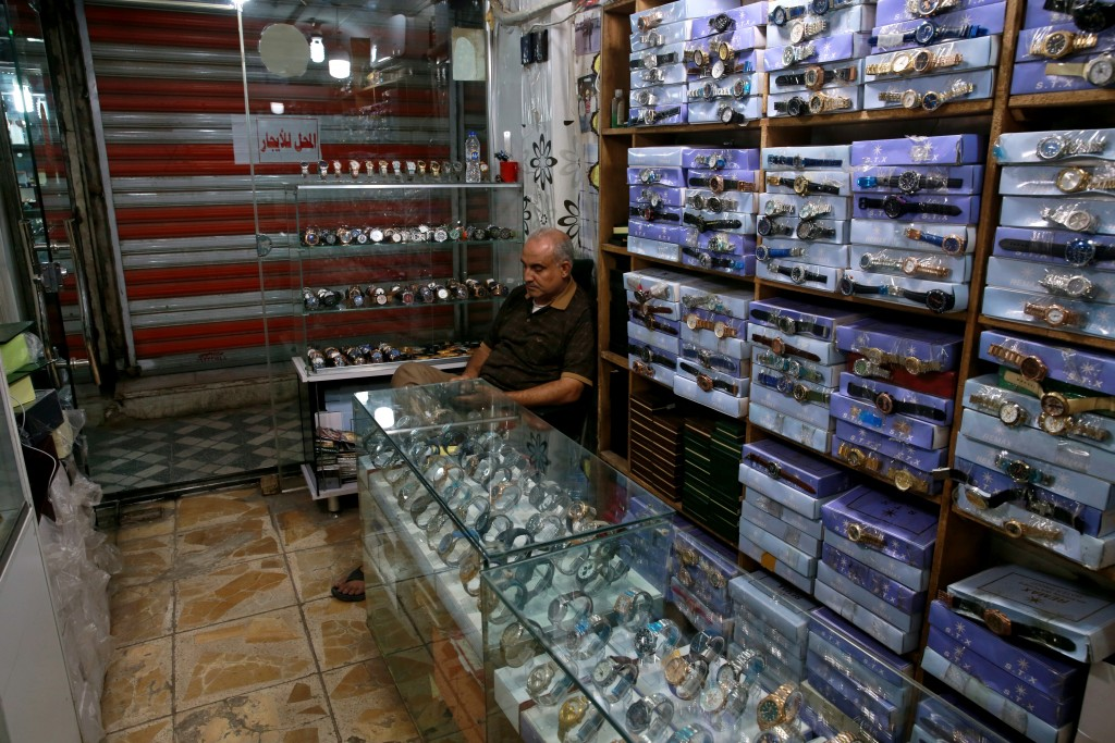 A shop owner waits for customers in Baghdad, Iraq, Tuesday, Oct. 20, 2020.  Iraq is in the throes of an unprecedented liquidity crisis, as the cash-st...