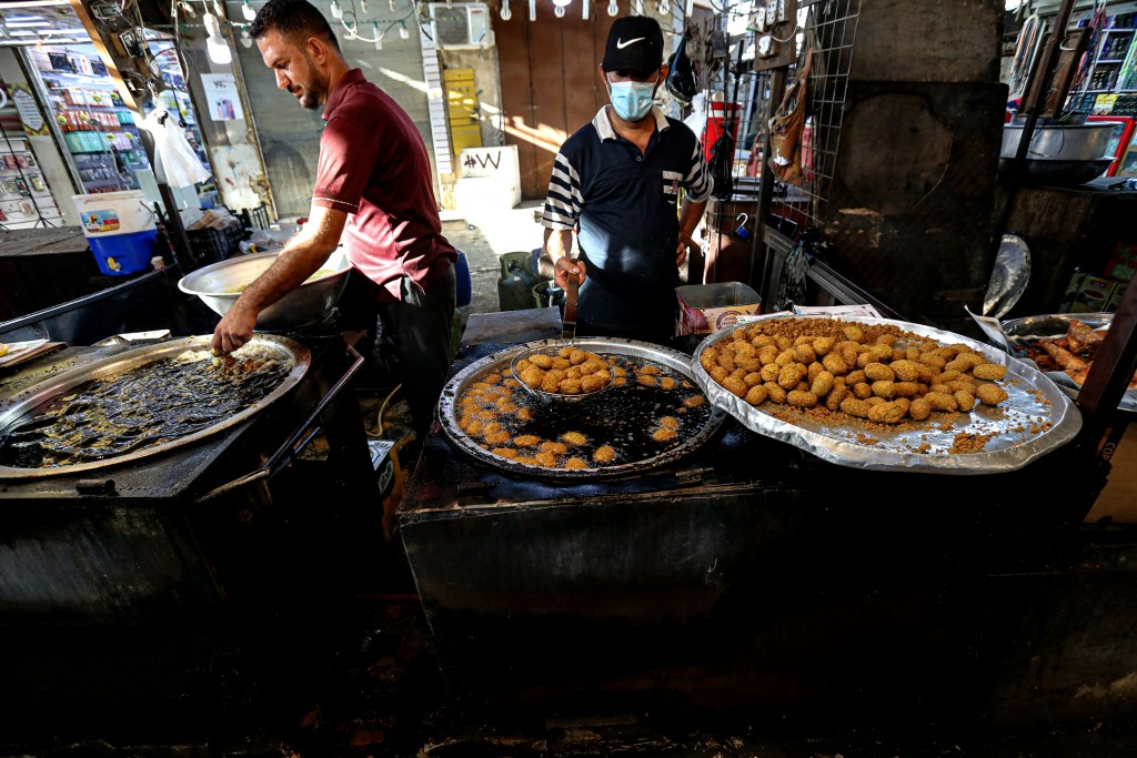 Street venders make traditional sweets at old Basra market, Iraq, Wednesday, Oct. 21, 2020.  Iraq is in the throes of an unprecedented liquidity crisi...