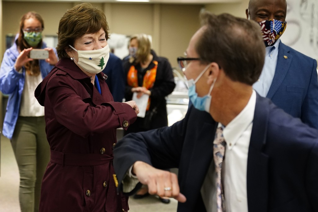 Sen. Susan Collins, R-Maine, left, bumps elbows with Scott Concannon, a worker at Day's Jewelers, Friday, Oct. 2, 2020, in Waterville, Maine. Collins,...