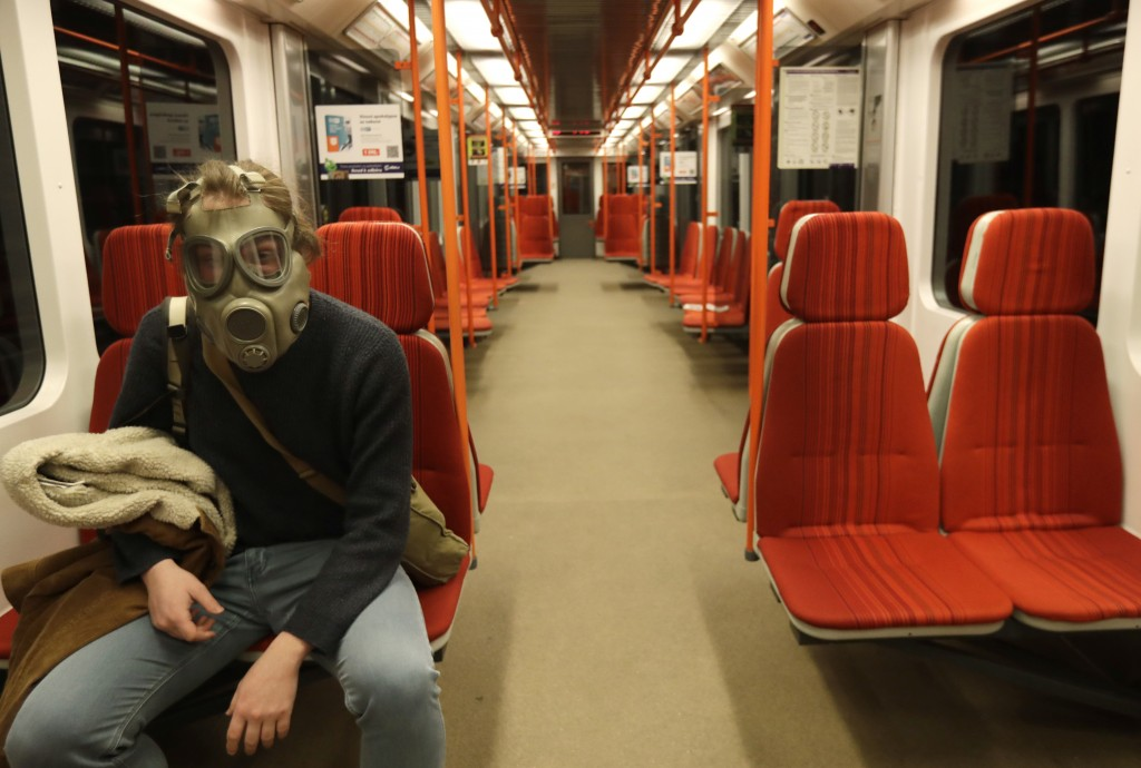 FILE - In this March 17, 2020 file photo a man wearing an old military gas mask rides the subway in Prague, Czech Republic. (AP Photo/Petr David Josek...