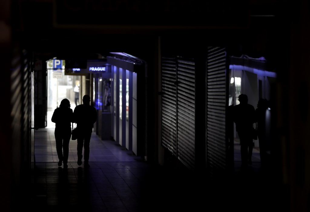 A couple walks past closed shops in downtown Prague, Czech Republic, Wednesday, Oct. 21, 2020. In another desperate attempt to slow the rise of corona...