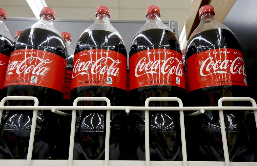 FILE- In this Aug. 8, 2018, file photo bottles of Coca-Cola sit on a shelf in a market in Pittsburgh.  The Coca-Cola Co. said on Thursday, Oct. 22, 20...