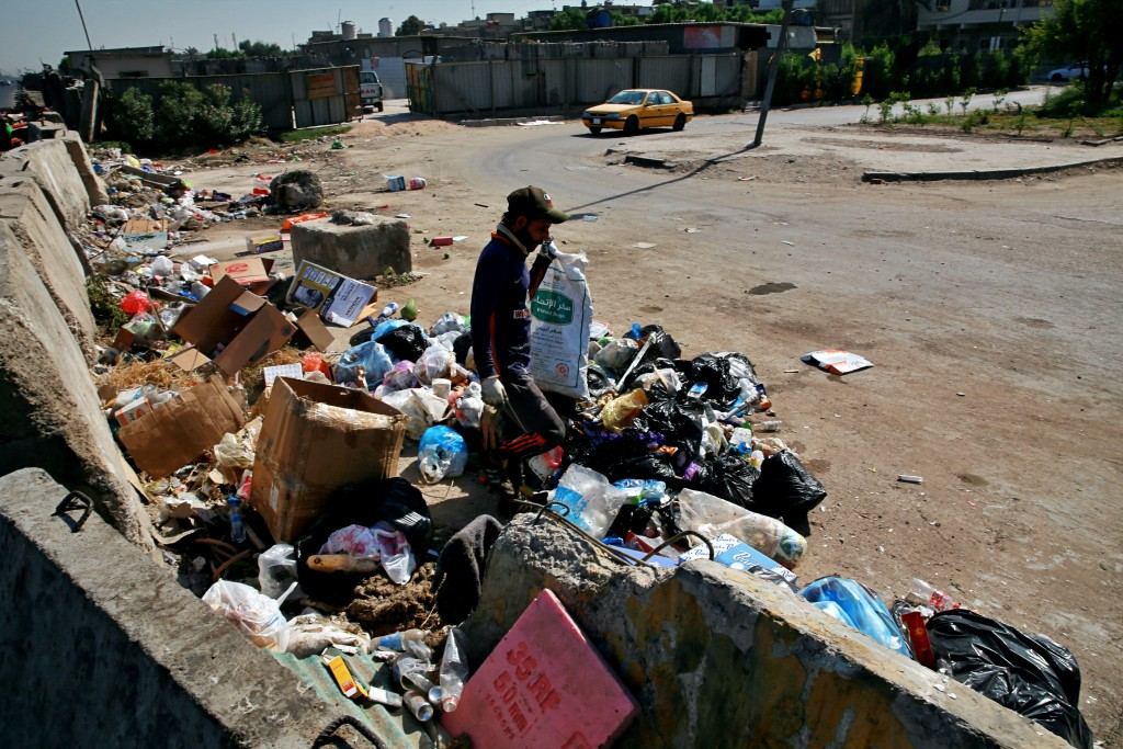 A man searches for recycled items in a landfill in Baghdad, Iraq, Tuesday, Oct. 20, 2020.  Iraq is in the throes of an unprecedented liquidity crisis,...