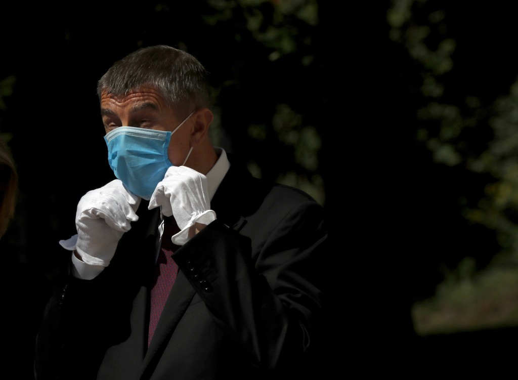FILE - In this June 3, 2020 file photo Czech Republic's Prime Minister Andrej Babis adjusts his face mask as he waits for the arrival of his Slovak co...