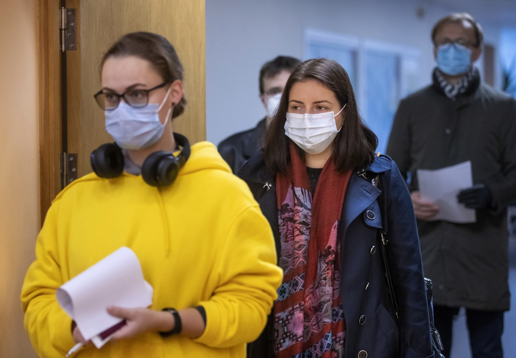 Lithuanian's, wearing face masks to protect against coronavirus, queue to cast their ballots at a polling station during early voting in the second ro...