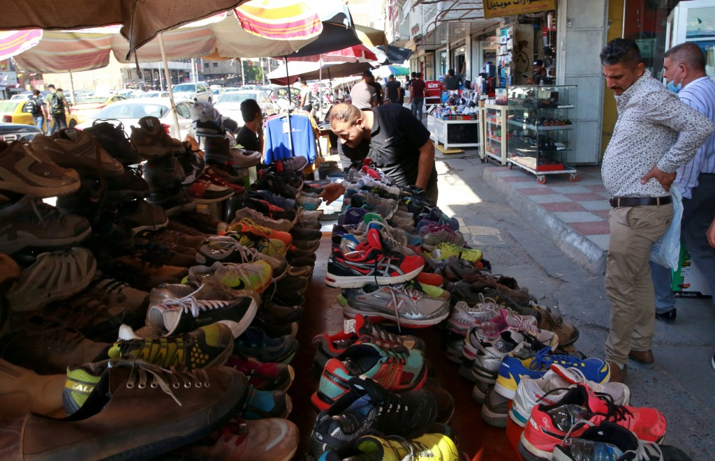 People shop for used shoes at the used-clothes market in Baghdad, Iraq, Tuesday, Oct. 20, 2020.  Iraq is in the throes of an unprecedented liquidity c...