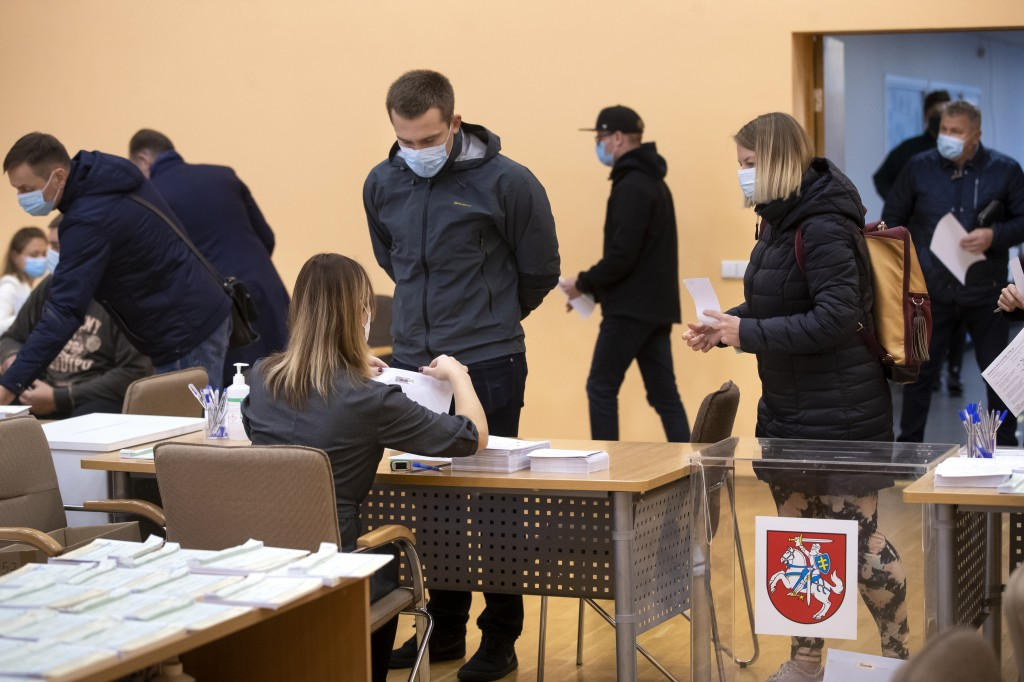 Lithuania's wearing face masks to protect against coronavirus, at a polling station during the early voting in the second round of a parliamentary ele...