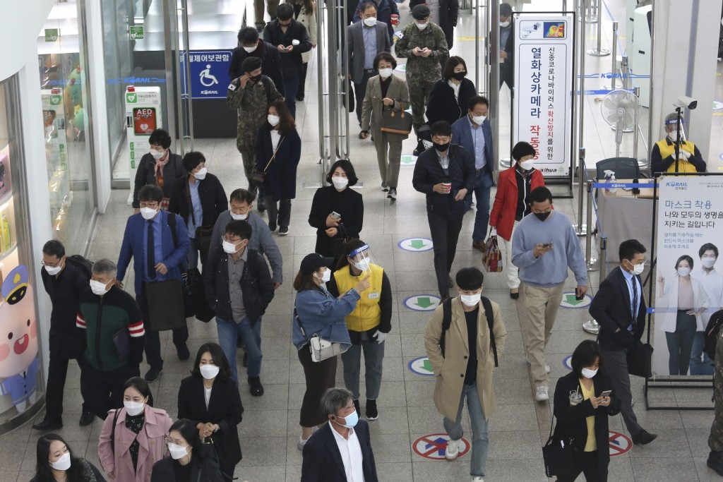 An employee, center right, wearing a face mask and face shield to help protect against the spread of the coronavirus, guides a passenger at the Seoul ...
