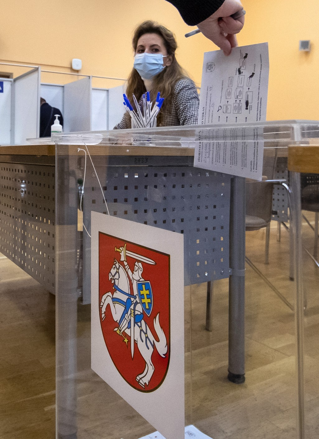 A man casts his ballot at a polling station during early voting in the second round of a parliamentary election in Vilnius, Lithuania, Thursday, Oct. ...
