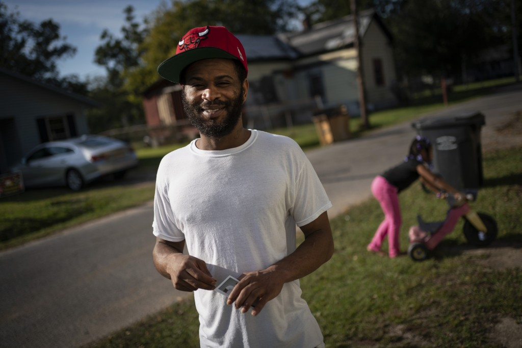 Demarkio Pritchett, 29, stands with his daughter Mariah Pritchett 8, playing in the background outside his grandmother's home, Tuesday, Oct. 6, 2020, ...