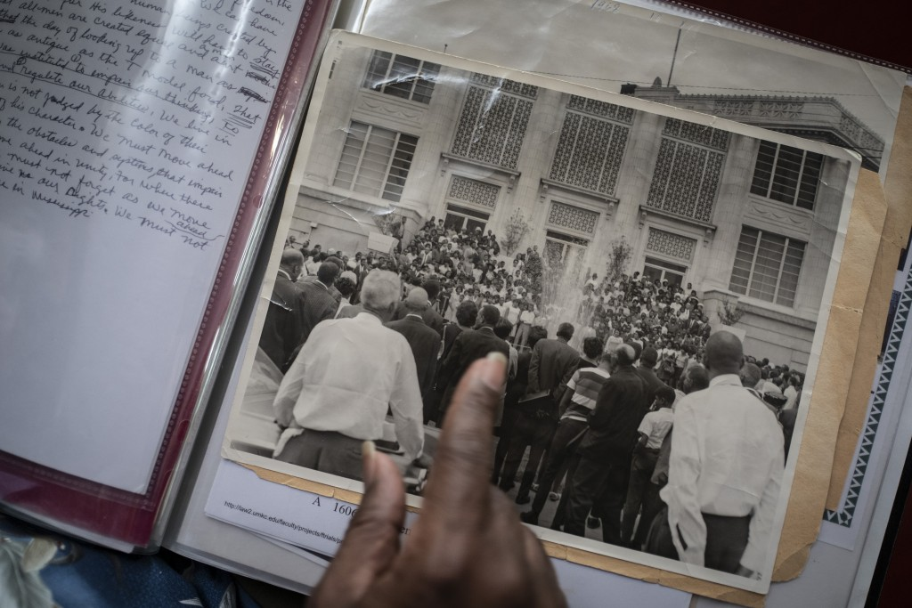 Rev. Charles Johnson, 82, points to an old photo of a gathering after the death of Rev. Martin Luther King Jr., during an interview with The Associate...