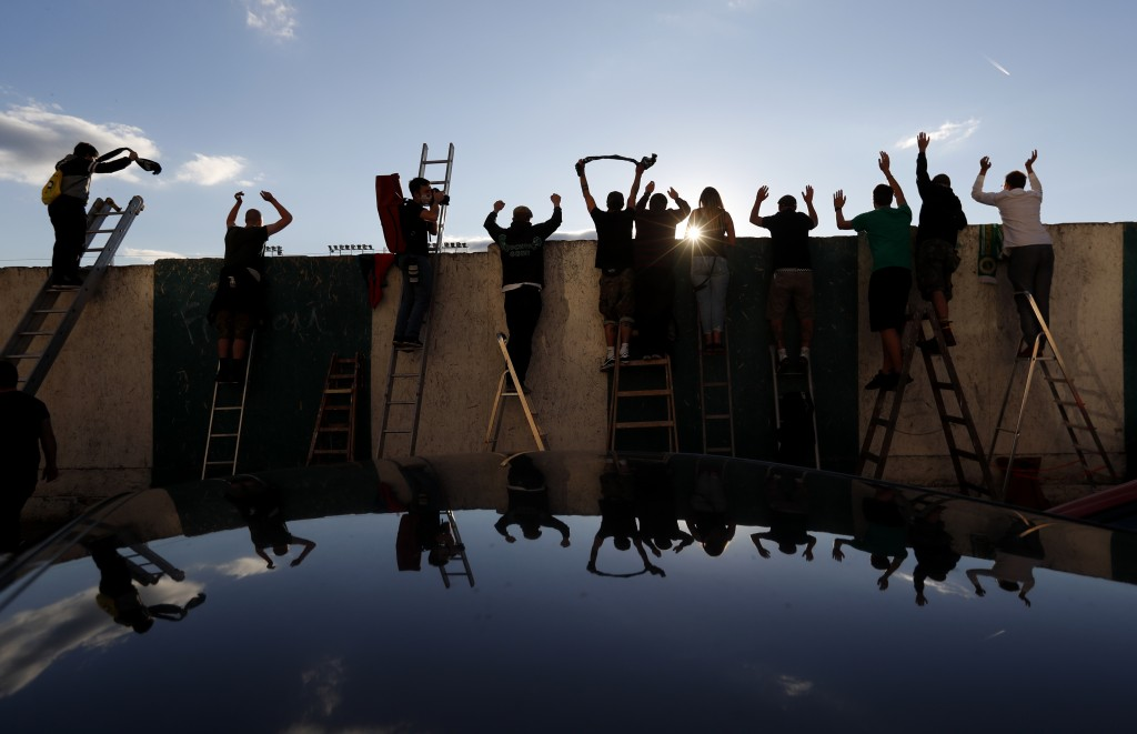 FILE - In this Oct. 4, 2020 file photo fans, standing on ladders from behind the fence, celebrate a goal as they watch a Czech first division match be...