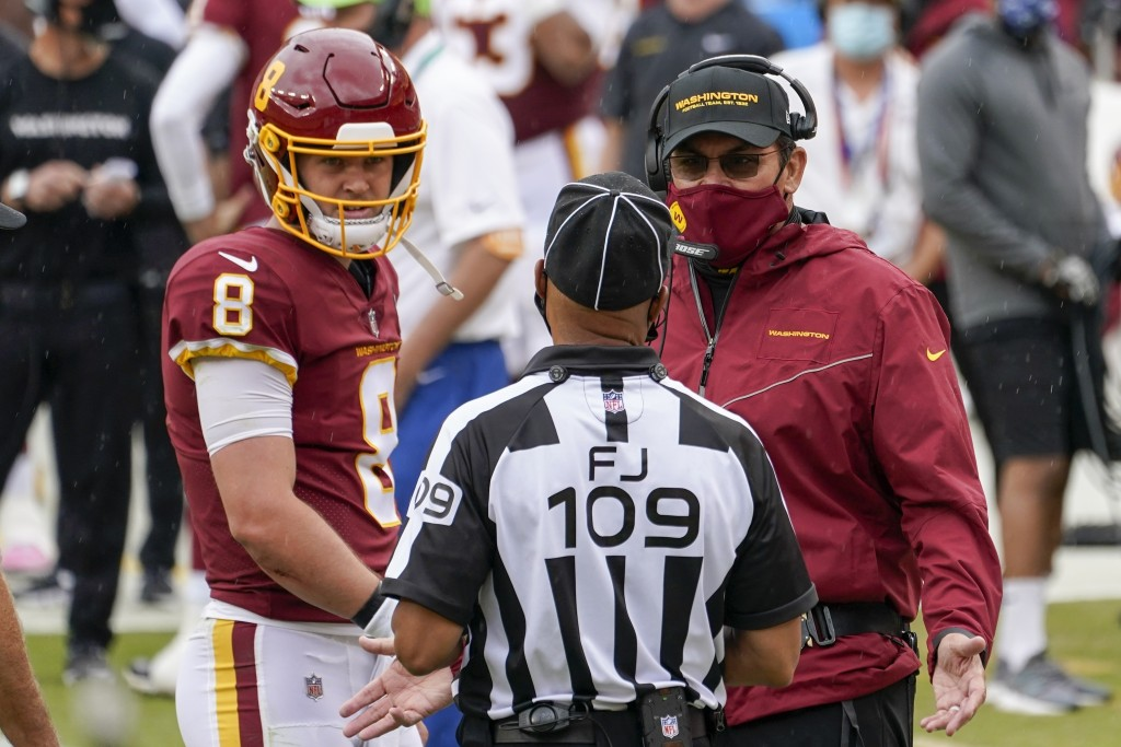 FILE - In this  Sunday, Oct. 11, 2020 file photo, Washington Football Team head coach Ron Rivera and quarterback Kyle Allen talk to field judge Dale S...