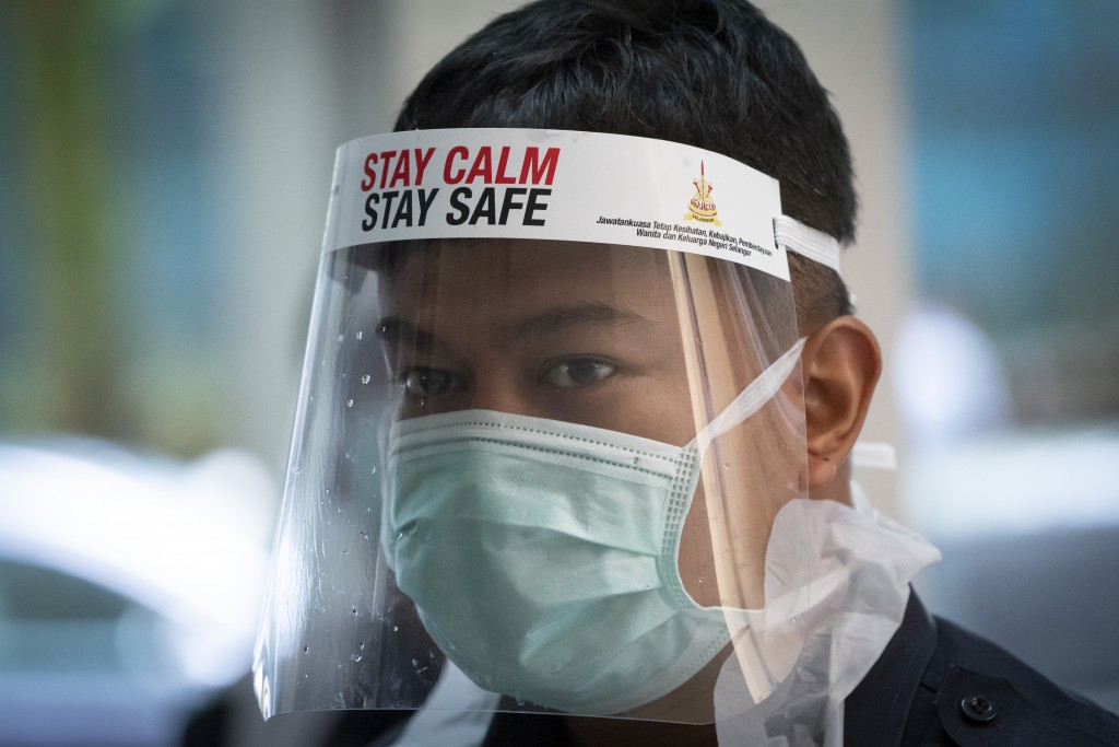 A healthcare staff member looks on as he arranges for residents to collect samples for coronavirus testing at an urban area in Bandar Utama, outskirts...
