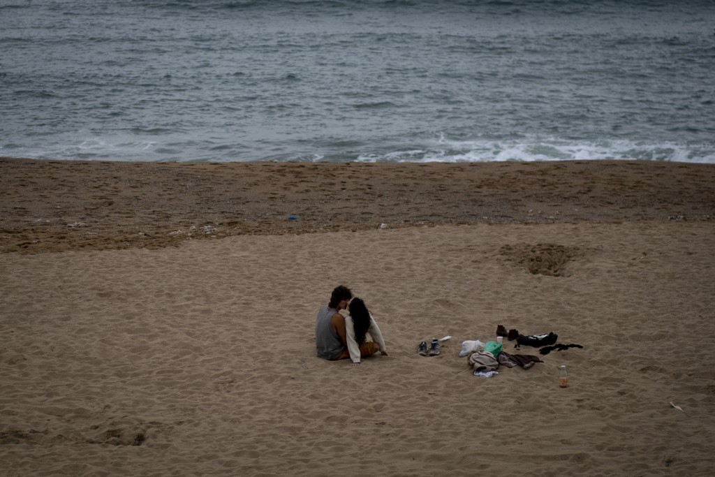 A couple kiss on a beach in Barcelona, Spain, Thursday, Oct. 22, 2020. Spain has reported 1 million confirmed infections — the highest number in Weste...