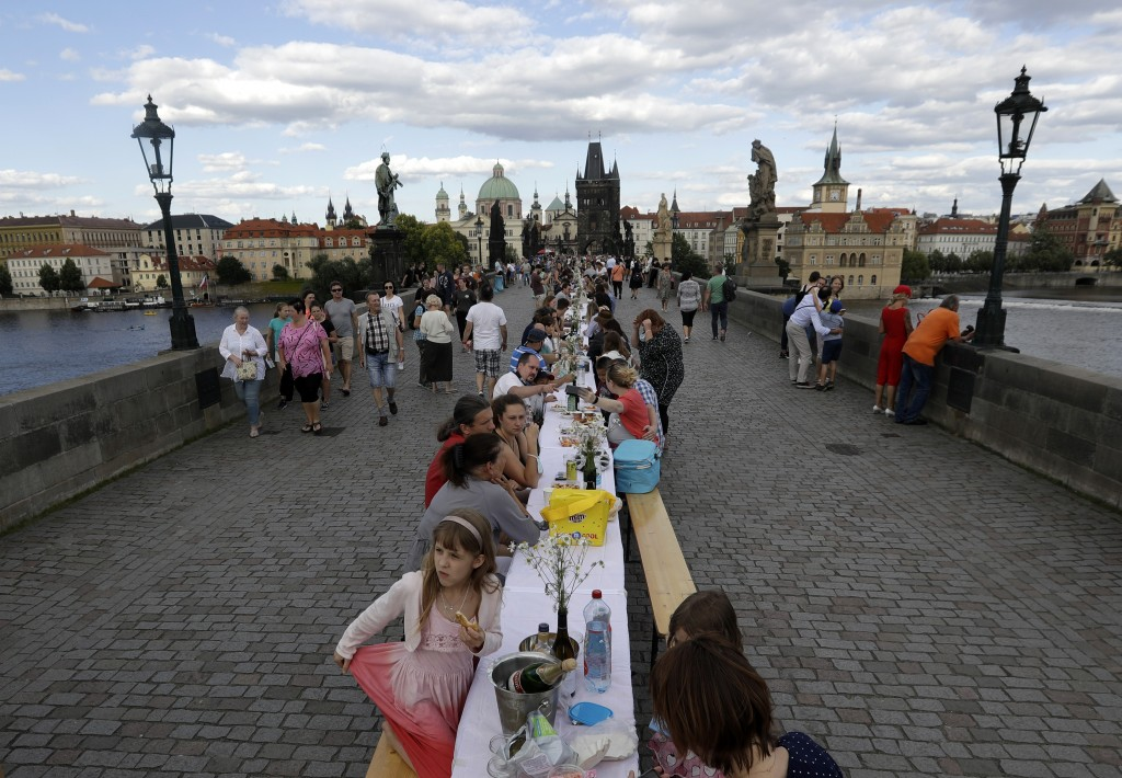 FILE - In this Tuesday, June 30, 2020 file photo, residents sit to dine on a 500 meter long table set on the medieval Charles Bridge, after restrictio...