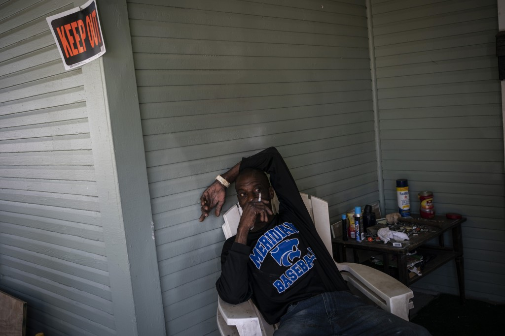 Gregory Blanchard, 53, a carpenter and painter relaxes with his cigarette on the front porch of his friend's home in Meridian, Miss. on Tuesday, Oct. ...