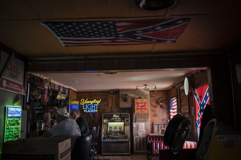 People sit in a bar decorated with an American flag and confederate flags before noon in Meridian, Miss., Wednesday, Oct. 7, 2020. Today, voters in Mi...