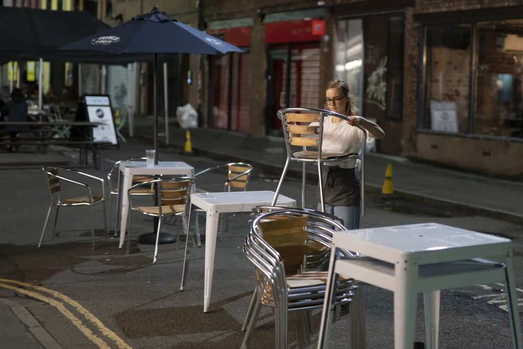 Furniture is cleared away outside a bar in Manchester's Northern Quarter as strict coronavirus restrictions on England's second-largest urban area, Gr...