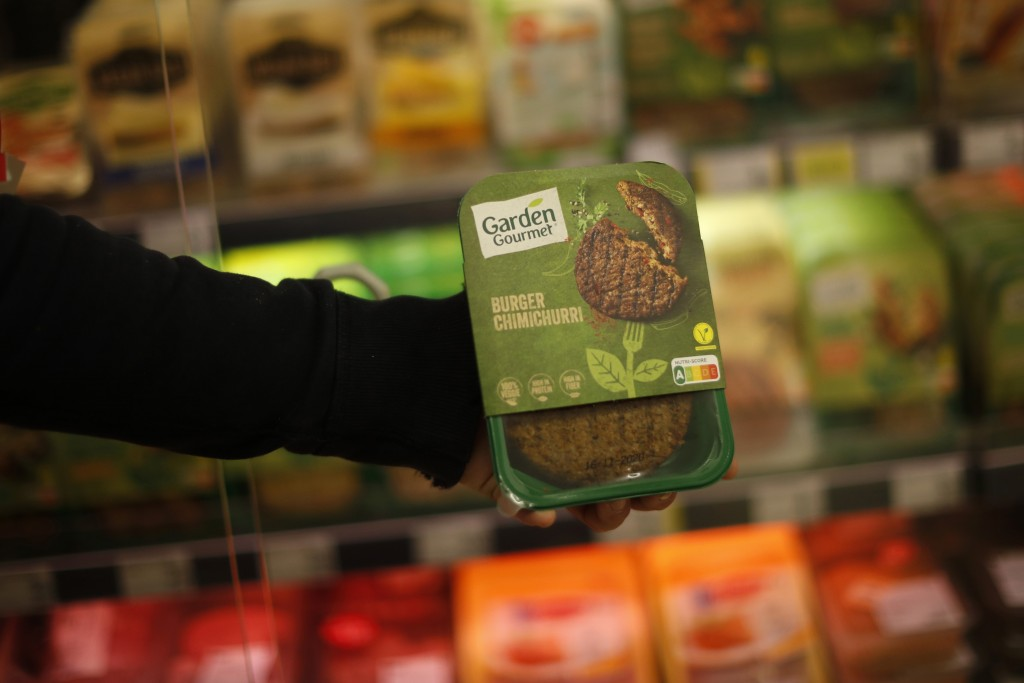 A store clerk shows a plant based burger at a supermarket chain in Brussels, Friday, Oct. 23, 2020. European lawmakers rejected Friday proposals that ...