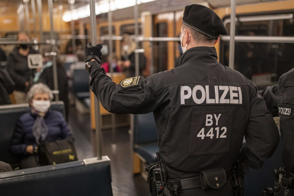Police officers and an employee of VAG (Verkehrs-Aktiengesellschaft Nuernberg) in a subway train to control the mask requirement, to avoid the spread ...