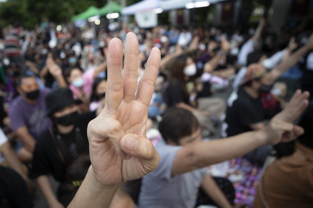 Pro-democracy activists flash three-fingered salutes outside remand prison, in which some of the activists are kept in Bangkok, Thailand, Friday, Oct....