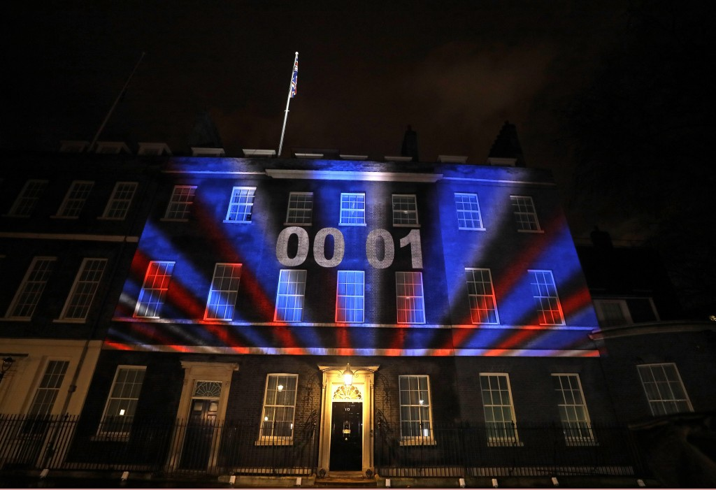 FILE - In this Friday, Jan. 31, 2020 file photo a countdown to Brexit timer and the colors of the British Union flag illuminate the exterior of 10 Dow...