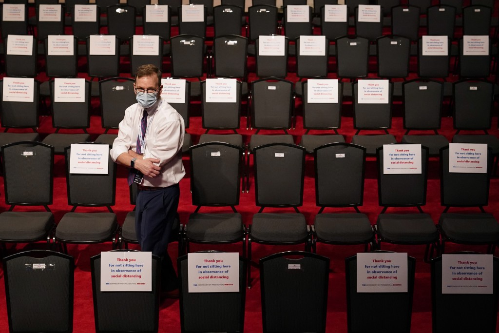 An official walks past spectator seating marked with signs observing social distancing requirments as preparations take place for the second President...
