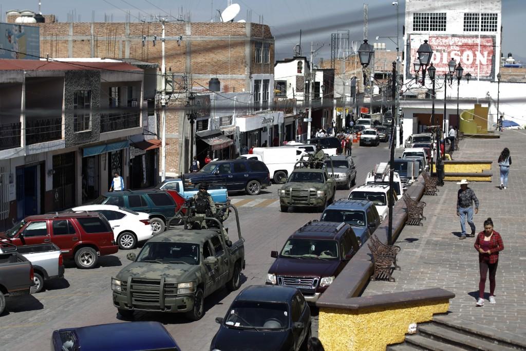 FILE - In this Feb. 10, 2020 file photo, National Guard patrol vehicles drive through the central square in Apaseo el Alto, Guanajuato state, Mexico. ...