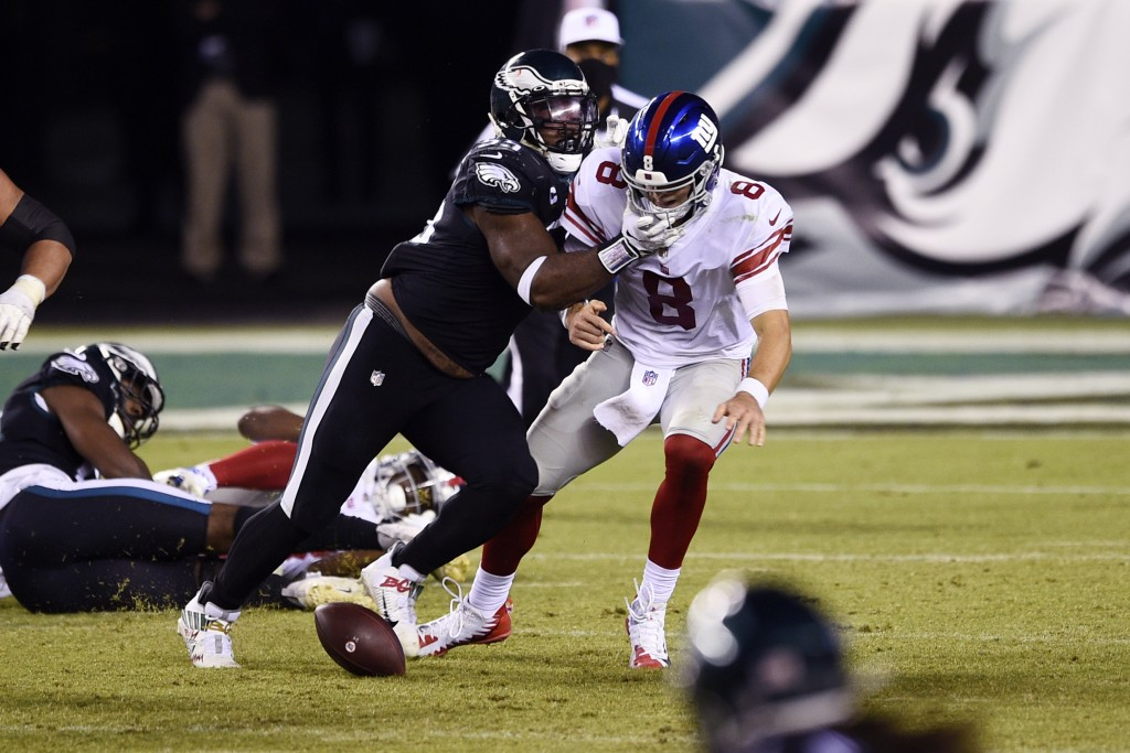 New York Giants' Daniel Jones (8) fumbles after being hit by Philadelphia Eagles' Brandon Graham (55) during the second half of an NFL football game, ...