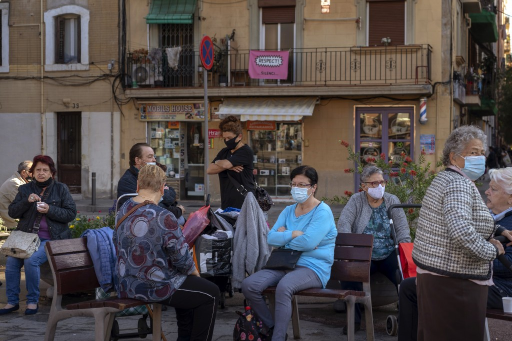People wearing face masks to protect from coronavirus, sit in a square in Barcelona, Spain, Friday, Oct. 23, 2020. Spain has reported 1 million confir...