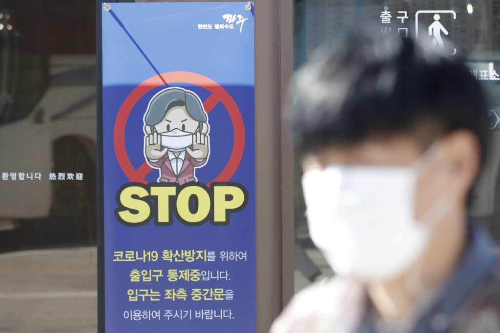 A man wearing a face mask walks past near a banner showing precaution against the coronavirus, at the Imjingak Pavilion in Paju, South Korea, Friday, ...