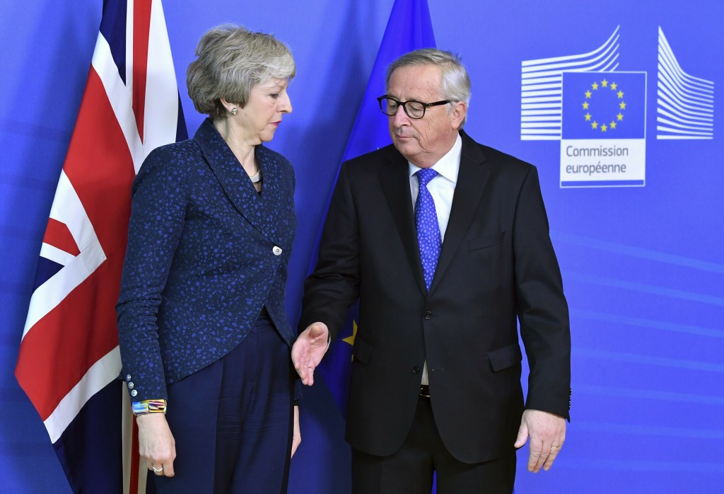 FILE - In this Thursday, Feb. 7, 2019 file photo European Commission President Jean-Claude Juncker prepares to shake hands with British Prime Minister...