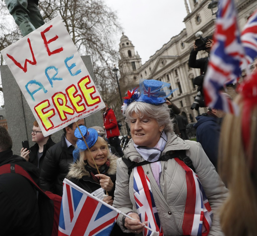 FILE - In this Friday, Jan. 31, 2020 file photo Brexiteers celebrate in London. Britain officially leaves the European Union on Friday after a debilit...