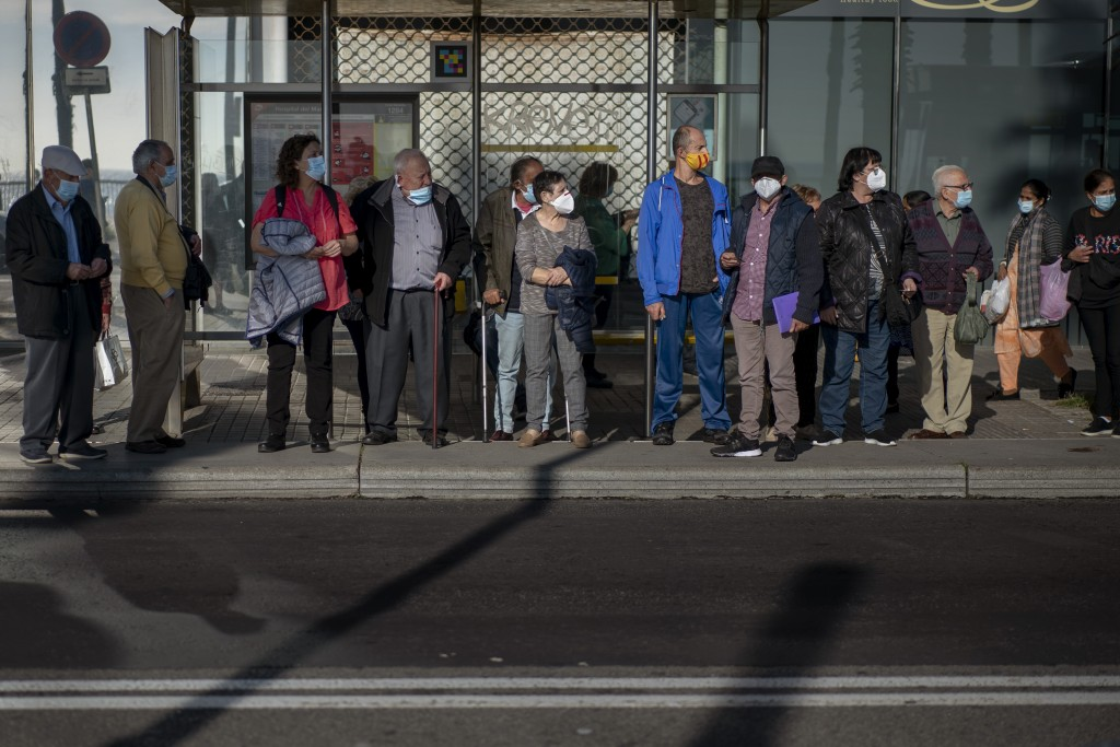 People wear face masks to protect from coronavirus as they wait for a bus in Barcelona, Spain, Friday, Oct. 23, 2020. Spain has reported 1 million con...