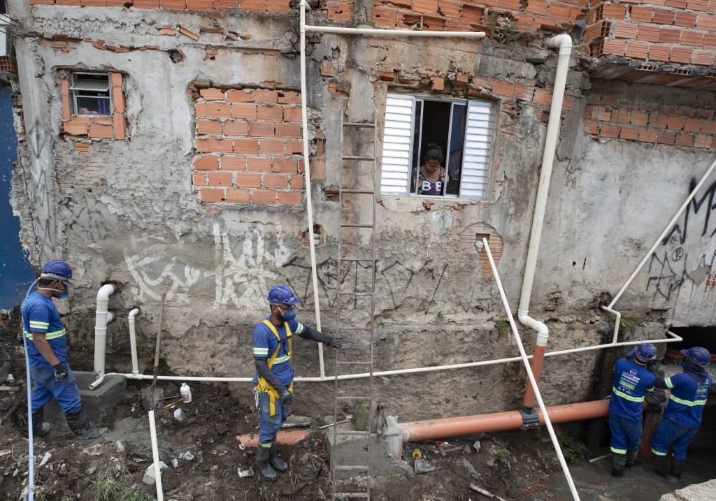 Men work to build a sewage system at the Americanopolis community, located near the Pinheiros River in Sao Paulo, Brazil, Thursday, Oct. 22, 2020. Aff...