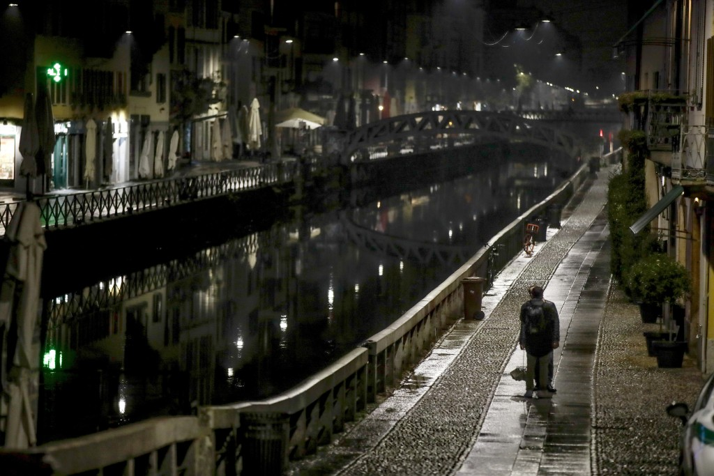The unusually empty Navigli area, a popular evening spot of restaurants and pubs bordering canals in Milan, Italy, Thursday, Oct. 22, 2020. Authoritie...