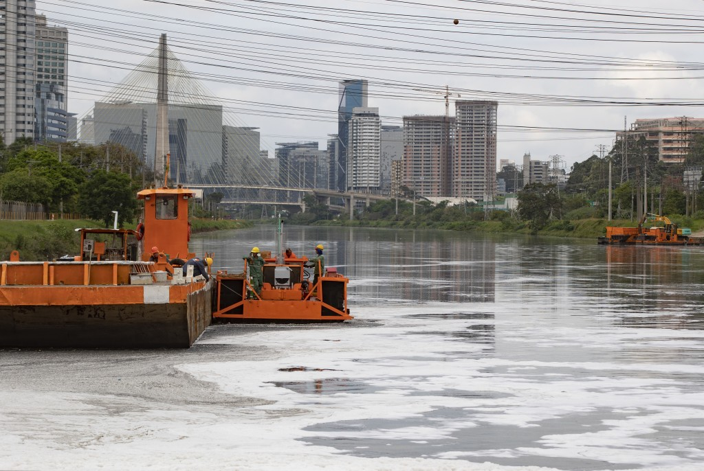 Men work on a cleaning river project where foam blankets a portion of the Pinheiros River in Sao Paulo, Brazil, Thursday, Oct. 22, 2020. Affected by d...