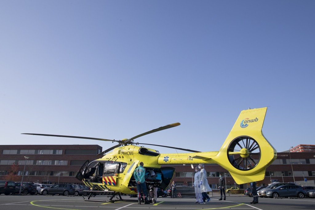 A COVID-19 patient is being carried into a helicopter at Flevoziekenhuis, or FlevoHospital, in Almere, Netherlands, Friday, Oct. 23, 2020. In the late...