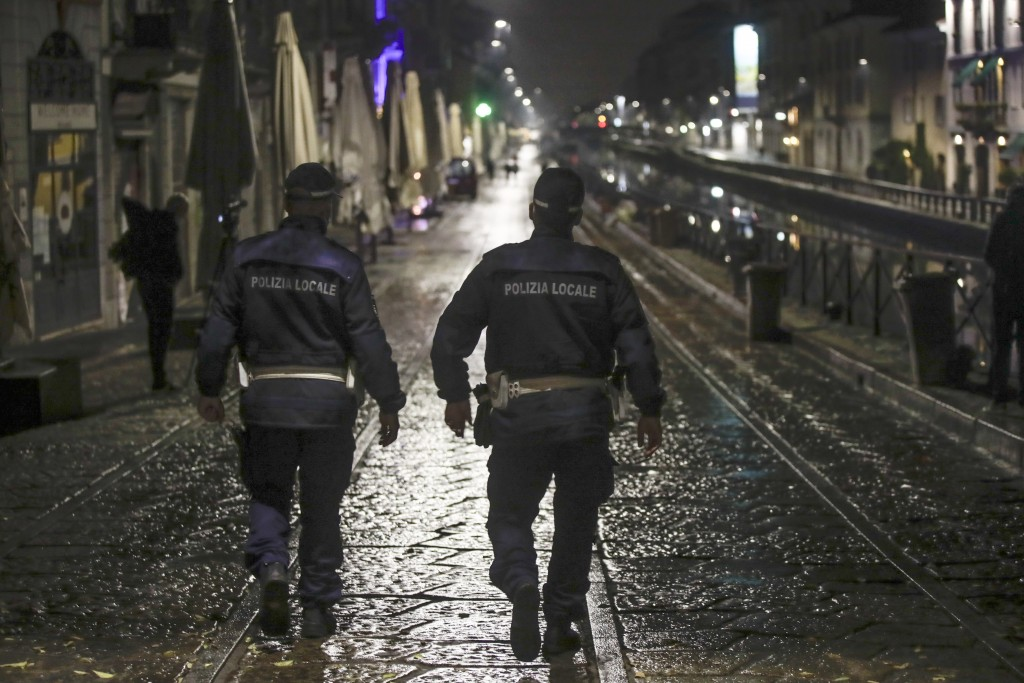Two city police officers patrol the Navigli area, a popular evening spot of restaurants and pubs bordering canals in Milan, Italy, Thursday, Oct. 22, ...