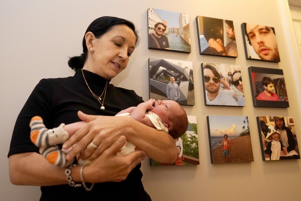 Mercedes Lemp poses for The Associated Press by holding her 2-day-old grandson near portraits of the newborn's father, Duncan Lemp, Friday, Oct. 16, 2...